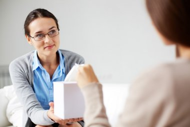 Psychiatrist giving  tissues to patient