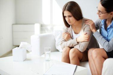 Psychiatrist comforting sad patient