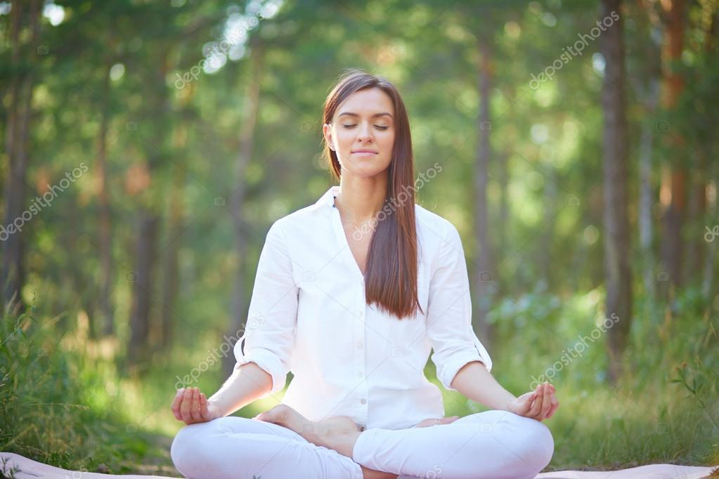 Woman sitting in pose of lotus
