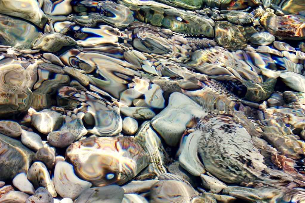 stones under  sunny water