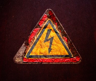 Old sign of high voltage on rusty metal surface