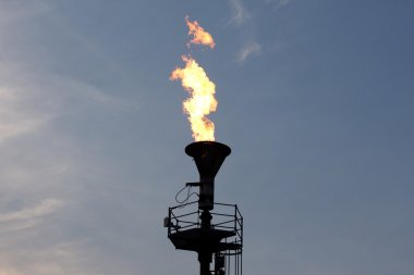 Oil burning torch against  blue sunset sky