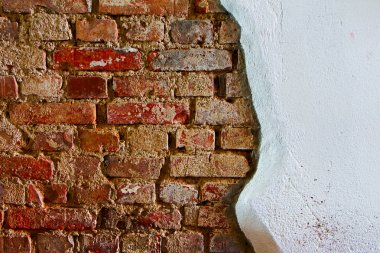Old plaster on a red brick wall