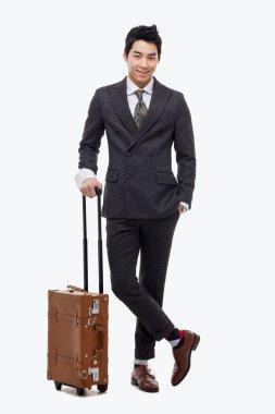 Businessman walking along pulling some travel luggage