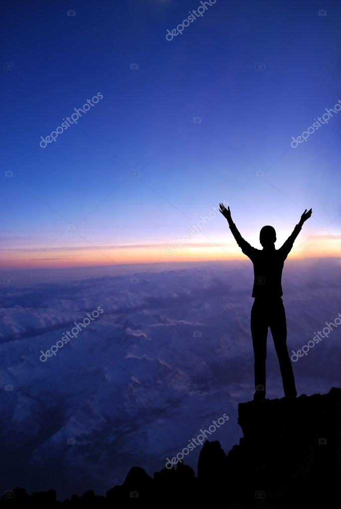 Woman on a top of a mountain at dawn