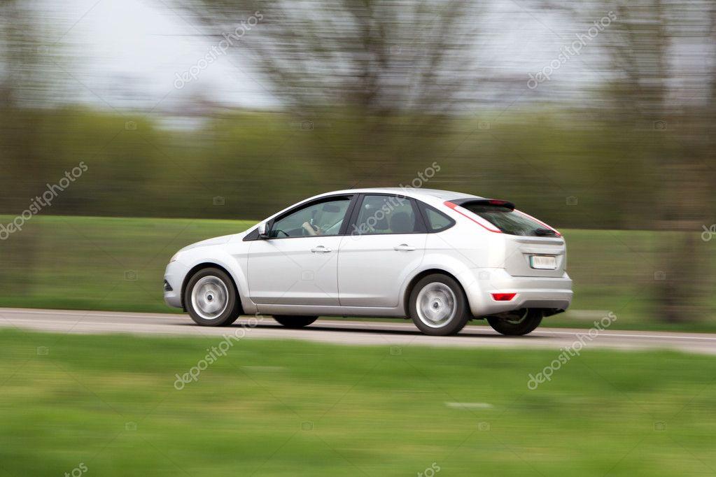 Silver hatchback car in motion blur