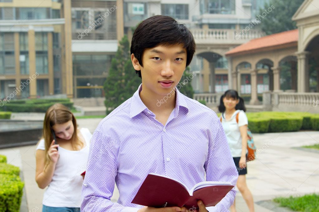 Portrait of young Asian man student carrying book and smiling