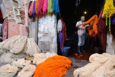 Man dyeing fabric in a market, Morocco