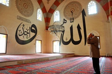 people praying in the mosque and Arabic writings
