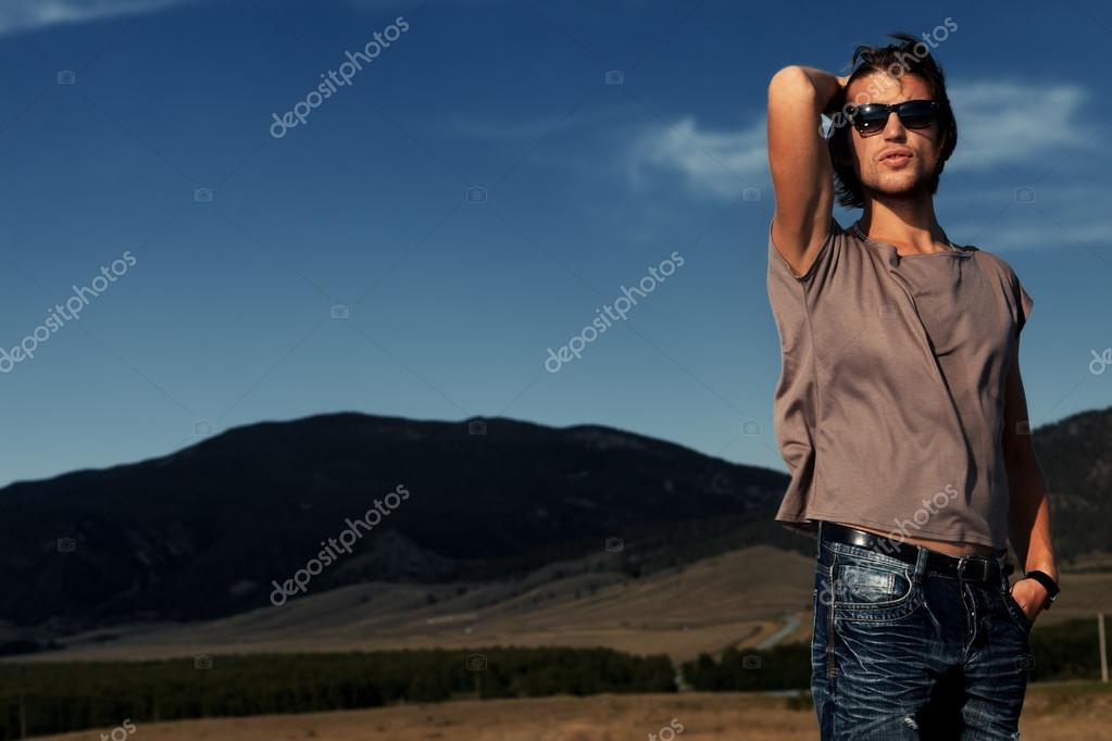 Handsome young man posing over picturesque landscape.