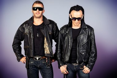Two brutal handsome men in leather jackets posing at studio. stock vector