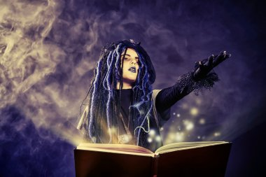 Little girl in a costume of witch casts a spell over magic book over dark background. stock vector