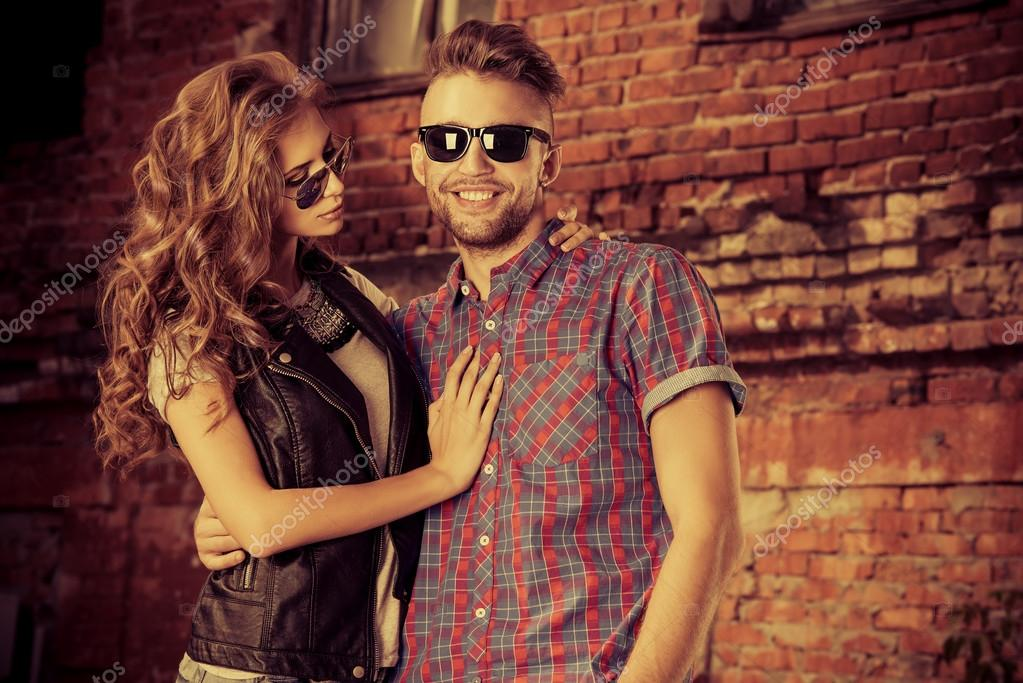 Couple of young people in jeans clothes posing outdoors over brick wall.