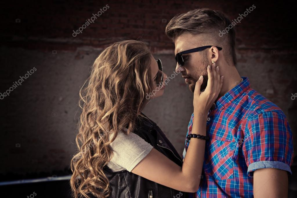 Romantic couple of young people in love posing outdoors over city background.