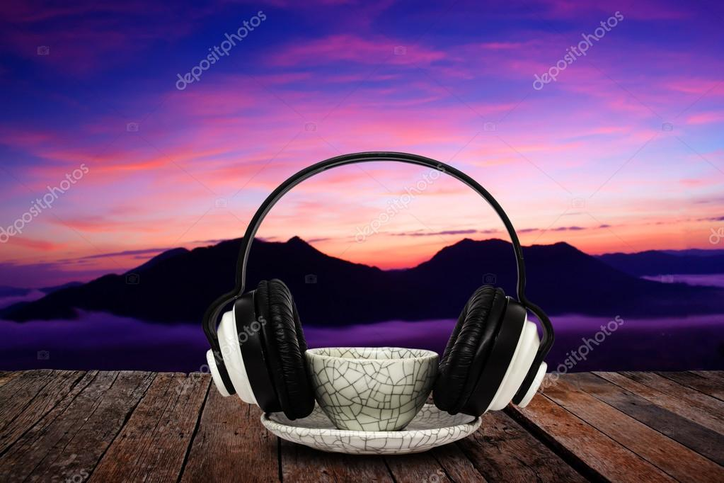 Coffee mug and headphone on wood floor against majestic mist and