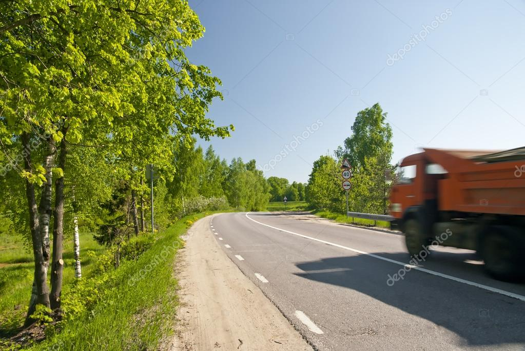 Dirt road with asphalt dump truck in motion