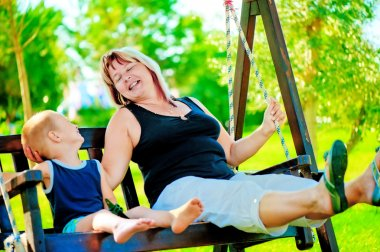 Happy grandmother and grandson on a swing