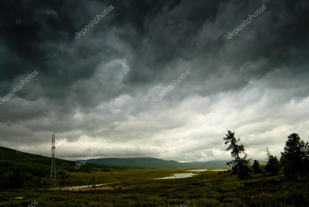 Black stormy sky in the rain in the mountains. Altai. Russia