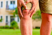 Muž, který držel ruce bolí kolena