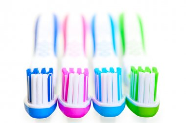 four new multi-colored toothbrushes are on a white background