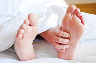 female legs sticking out from under the covers and cards hand