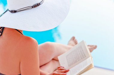 Girl in a hat reading a book near the pool, sitting in a lounge chair