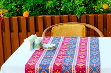 a table covered with a cloth with oriental patterns