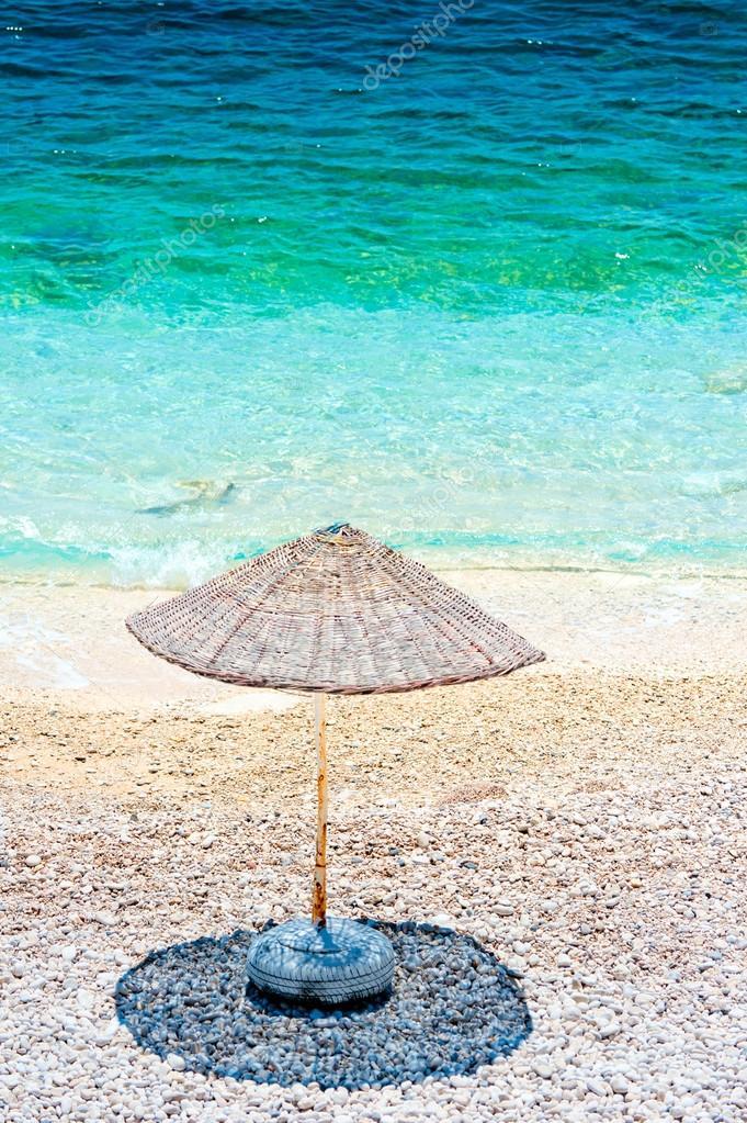 lonely beach umbrella casts a shadow