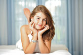Portrait of smiling beautiful teen girl at home in white dress and relaxing on comfortable bed. Luxury interior.