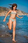 Fiatal tini lány játszik a hullámok a tengerparton. Fürdőruha, fuss a strandon tini lány