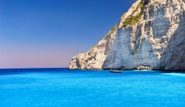 Boat anchored on Navagio beach (also known as shipwreck beach), Zakynthos island, Greece.Side view of Navagio beach in Greece with cruiser anchoring next to beach