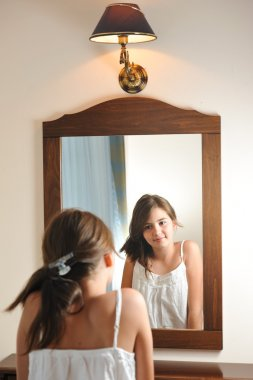 A beautiful teen girl studies her appearance as she looks into the mirror at her beautiful young reflection. Teen girl happy with their appearance in the mirror