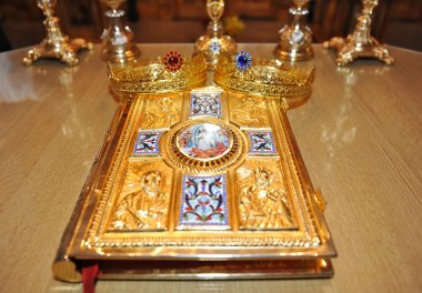 Crosses, rings and crowns of gold on the table in church.