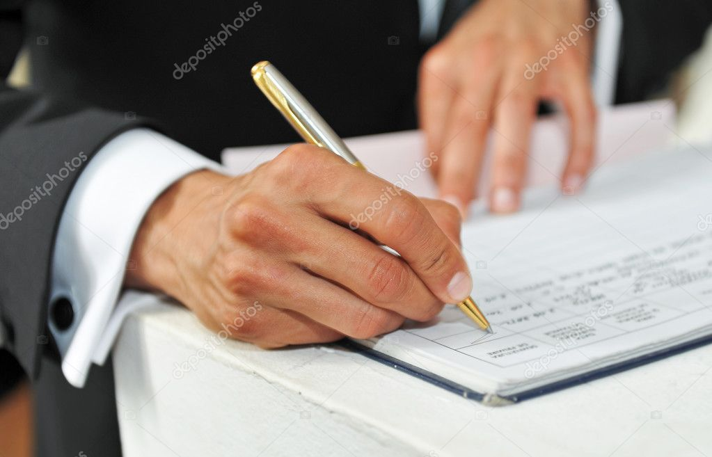 Business man signing a contract on a white table.