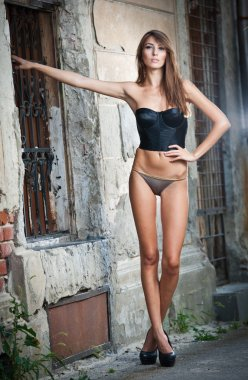 sexy girl in bikini posing fashion near red brick wall on the street.Shot of a sexy high fashion woman posing outdoor. Cute brunette with black bra posing on a city street