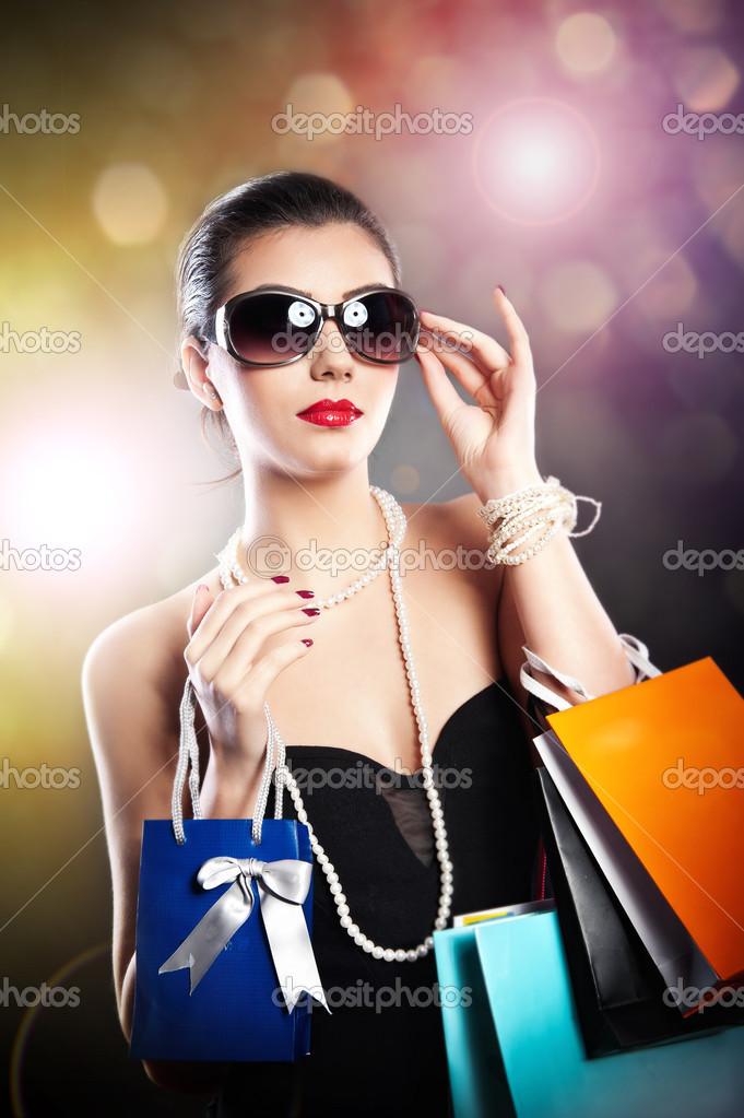 4872a51a7b Γυναίκα με γυαλιά κρατώντας τσάντες αγορών σε μαύρο background.style  ομορφιά κορίτσι με ψώνια bags.portrait εκπληκτική νεαρής γυναίκας σε γυαλιά  ηλίου που ...