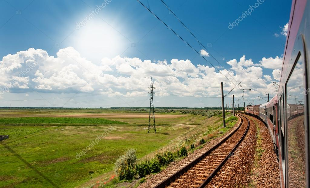 Railway goes to horizon in green and yellow landscape under blue sky with white clouds.railway under cloudy sky.Scenic railroad in rural area in summer and blue sky with white clouds.