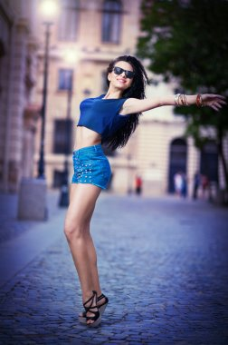 Portrait of a beautiful sexy woman with denim shorts and sunglasses in urban background . Attractive female brunette woman posing in blue jeans short in urban scene .Young woman in blue jeans short