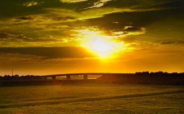 Sunset with dramatic sky over agricultural green field with a bridge. Green field and bridgeat the sunset. Wheat field at sunset
