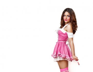 Attractive brunette girl with a lollipop in her hand and pink dress