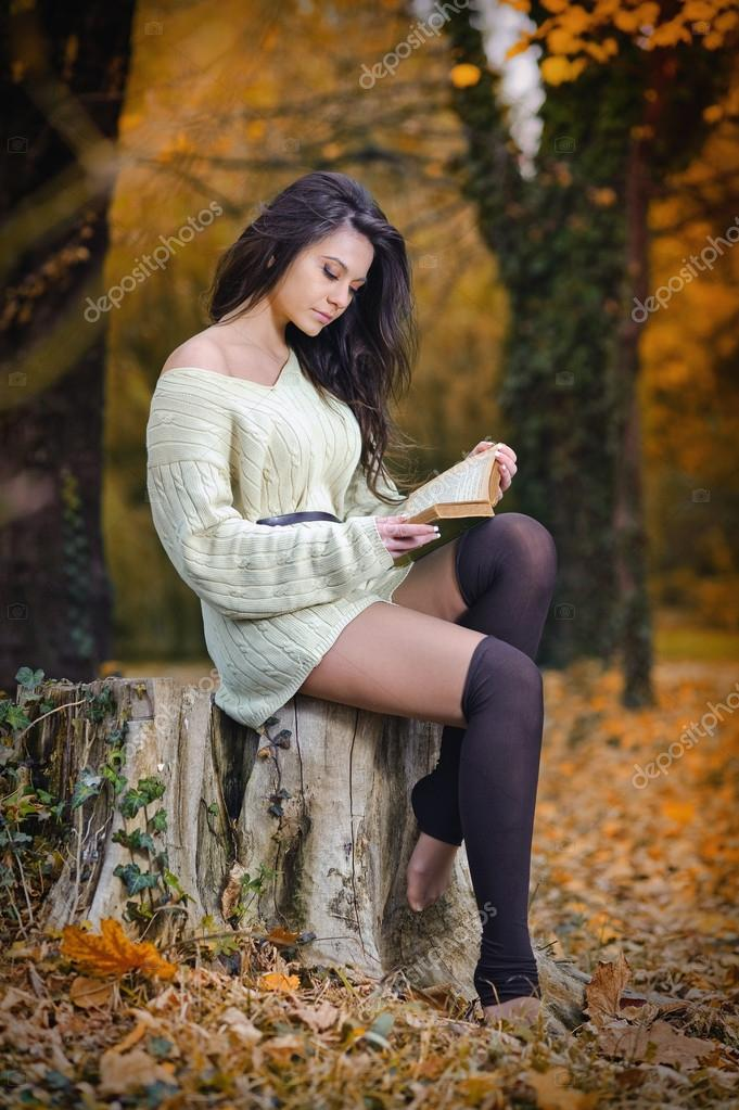 Young Caucasian sensual woman reading a book in a romantic autumn scenery. Portrait of pretty young girl in the forest in autumn day. Fashion portrait of a beautiful young woman in autumn forest