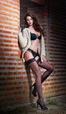 Beautiful brunette woman in black sensual lingerie posing provocatively in front of a brick wall. Young model wearing black stockings posing pretty. Caucasian model standing near red brick wall