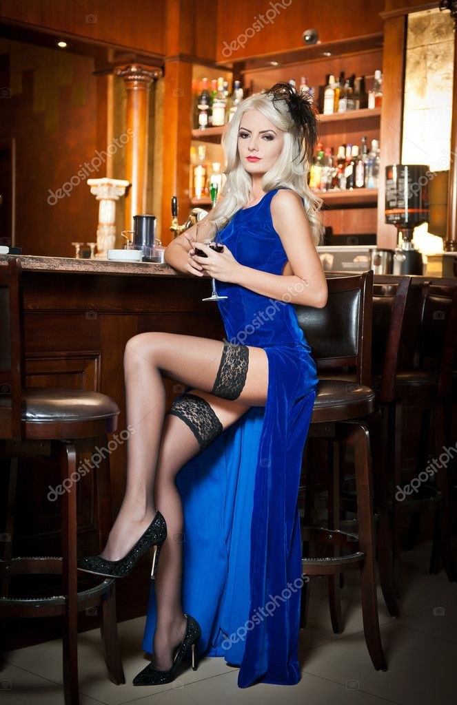 Attractive Blonde Woman In Elegant Blue Long Dress Sitting
