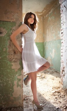 Beautiful girl posing fashion near an old wall. Pretty young woman posing laying on a wall. Very attractive blonde girl with a transparent white short dress. Romantic young woman posing