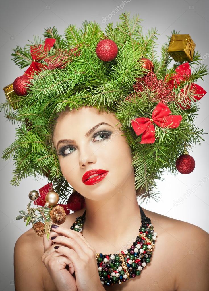 Beautiful creative Xmas makeup and hair style indoor shoot. Beauty Fashion Model Girl. Winter. Beautiful fashionable in studio. Attractive girl with Christmas tree accessories. Luxuriant. Femininity.