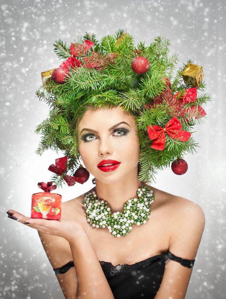 Beautiful creative Xmas makeup and hair style indoor shoot. Beauty Fashion Model Girl. Winter. Beautiful attractive girl with Christmas tree accessories in studio holding a gift.