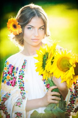 Young girl wearing Romanian traditional blouse holding sunflowers outdoor shot. Portrait of beautiful blonde girl with bright yellow flowers bouquet. Beautiful woman with yellow flower in hair posing