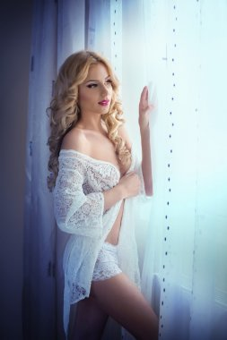 Attractive sexy blonde with white lace lingerie near the curtains looking on the window. Portrait of sensual long fair hair woman wearing white bra and panties in classic scene. Beautiful woman