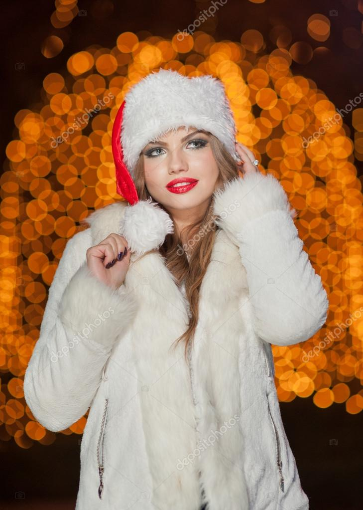 07d4c780a0a5 Fashionable lady wearing Xmas hat and white fur coat outdoor ...