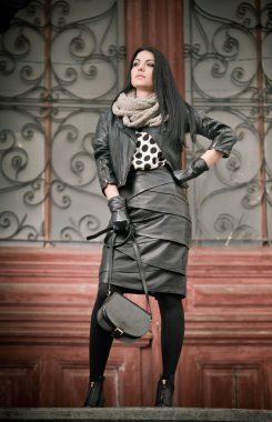 Attractive young woman in winter fashion shot with wrought iron decorated doors in background. Beautiful fashionable female - black leather outfit. Elegant long hair brunette posing in urban scenery.